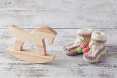 Newborn announcement template. Handmade knitted booties with toy Royalty Free Stock Photos