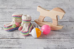 Newborn announcement template. Handmade knitted booties with toy Stock Photos