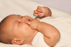 Newborn Asian baby girl lying on a bed. Stock Image