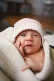 Newborn baby. Close up of newborn baby girl wearing a pink hat looking at camera Royalty Free Stock Photography
