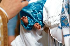 Newborn baby baptism in the church, small bare legs in blue pants royalty free stock images