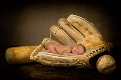 Newborn baby in baseball glove Stock Image