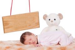 Newborn baby. Beautiful female newborn baby sleeping with name board and bear Royalty Free Stock Image