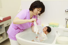 Newborn baby. Being bathed by a nurse Stock Image