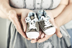 Newborn baby booties in parents hands Stock Photos