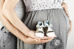 Newborn baby booties in parents hands, Pregnant woman belly stock image