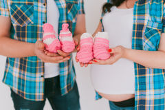 Newborn baby booties in parents hands. Closeup Stock Images