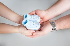 Newborn baby booties in parents hands. Pregnancy. royalty free stock images
