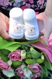 Newborn baby booties in parents hands. royalty free stock photo