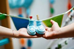 Newborn baby booties in parents hands, pregnant woman belly, blue shoes hanging on a string with decorative clothespins with a hea stock photos