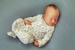 Newborn baby boy asleep on a blue background in white pajamas wi Stock Photos