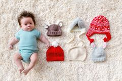 Newborn baby boy with assorted baby hats royalty free stock photography