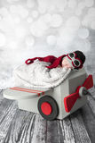 Newborn baby boy in aviator outfit in a plane. A newborn baby boy in an aviator outfit sleeps in a prop plane Royalty Free Stock Images
