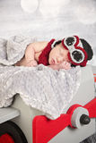 Newborn baby boy in aviator outfit in a plane. A newborn baby boy in an aviator outfit sleeps in a prop plane Stock Photos