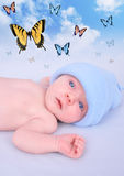Newborn Baby Boy Butterfly Dream. A newborn baby boy is wearing a blue hat on a soft blue background. Butterfly's are in the sky fluttering. Use for a Stock Photos