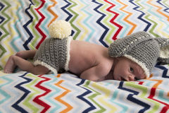 Newborn baby boy on chevron blanket in bunny outfit stock image
