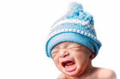 Newborn baby boy crying & screaming. Wearing blue hat isolated in white background Royalty Free Stock Image