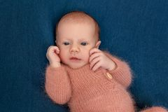 Newborn baby boy 14 days wearing knitted suit sleeping in bed close-up. royalty free stock image