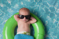Newborn Baby Boy Floating on an Inflatable Swim Ring. Four week old newborn baby boy sleeping on a tiny inflatable swim ring. He is wearing crocheted board Royalty Free Stock Image