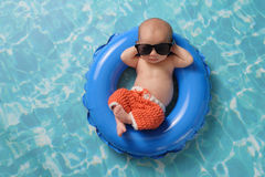 Newborn Baby Boy Floating on an Inflatable Swim Ring. Four week old newborn baby boy sleeping on a tiny inflatable swim ring. He is wearing crocheted board Royalty Free Stock Images