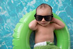 Newborn Baby Boy Floating on a Swim Ring. Two week old newborn baby boy sleeping on a tiny, green, inflatable swim ring. He is wearing green, crocheted board stock image