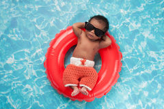 Newborn Baby Boy Floating on a Swim Ring. Two week old newborn baby boy sleeping on a tiny inflatable swim ring. He is wearing crocheted board shorts and black