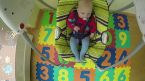 Newborn baby boy or girl sway in colorful swing at home. 4K stock video footage
