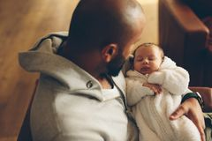 Newborn baby boy in his father`s arms. Top view shot of newborn baby boy in his father`s arms. Man sitting at home with his son stock photo
