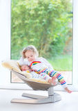 Newborn baby boy and his sister relaxing in swing Royalty Free Stock Photo