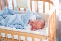 Newborn baby boy in hospital cot. Newborn baby in hospital room. New born child in wooden co-sleeper crib. Infant sleeping in bedside bassinet. Safe co-sleeping Stock Photo