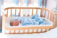 Newborn baby boy in hospital cot. Newborn baby in hospital room. New born child in wooden co-sleeper crib. Infant sleeping in bedside bassinet. Safe co-sleeping Stock Image