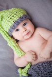 Newborn baby boy with knitted hat. Baby boy with green and grey knitted hat - focused Royalty Free Stock Image