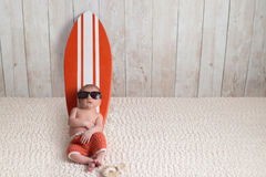 Newborn Baby Boy Leaning on Surfboard stock photos