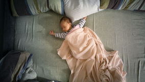 Newborn baby boy lying on big parents bed. View from top Royalty Free Stock Photos