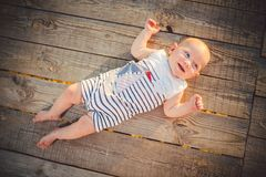 Newborn baby boy one year blond lying on his back on a wooden background wharf, pier in striped clothes view from above, compineis royalty free stock photo