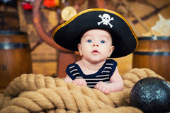 Newborn baby boy in a pirate hat is on the ropes. The interior of the ship`s deck Royalty Free Stock Images
