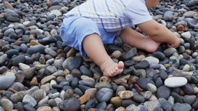 Newborn baby boy plays at the windy seaside with stones. Toddler plays at the windy seaside stock video