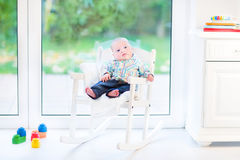 Newborn baby boy in rocking chair next window Royalty Free Stock Photo