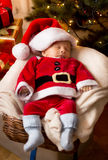 Newborn baby boy in Santa Claus costume sleeping in basket Stock Image