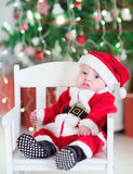 Newborn baby boy in Santa outfit sitting under Chr. Cute newborn baby boy in a Santa outfit sitting under a decorated Christmas tree in a white rocking chair stock photo