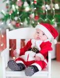 Newborn baby boy in Santa outfit sitting under Chr stock photo