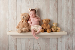 Newborn Baby Boy on a Shelf with Teddy Bears Stock Photo