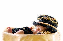 Newborn baby boy sleeping in basket. Wearing black and brown hat and blanket isolated in white background Stock Images