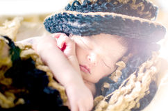 Newborn baby boy sleeping in basket. Wearing black & brown hat and blanket isolated in white background Royalty Free Stock Photography