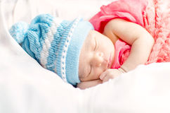 Newborn baby boy sleeping in basket. Wearing blue hat and red blanket isolated in white background Royalty Free Stock Photography