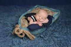 Newborn Baby Boy Sleeping in a Boat Stock Photo