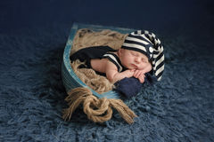 Newborn Baby Boy Sleeping in a Boat. Portrait of a two week old newborn baby boy. He is sleeping in a miniature boat and wearing a dark blue and white striped Stock Photography