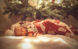 Newborn baby boy sleeping and dreaming under christmas tree wrapped at sleeping christmas bag stock photos