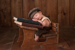 Newborn Baby Boy Sleeping at his School Desk. Three week old newborn baby boy wearing crocheted cap, shorts and suspenders. He is sitting at a tiny school desk Stock Images
