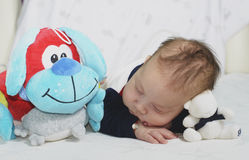 Newborn baby boy sleeping with his toys Stock Photo